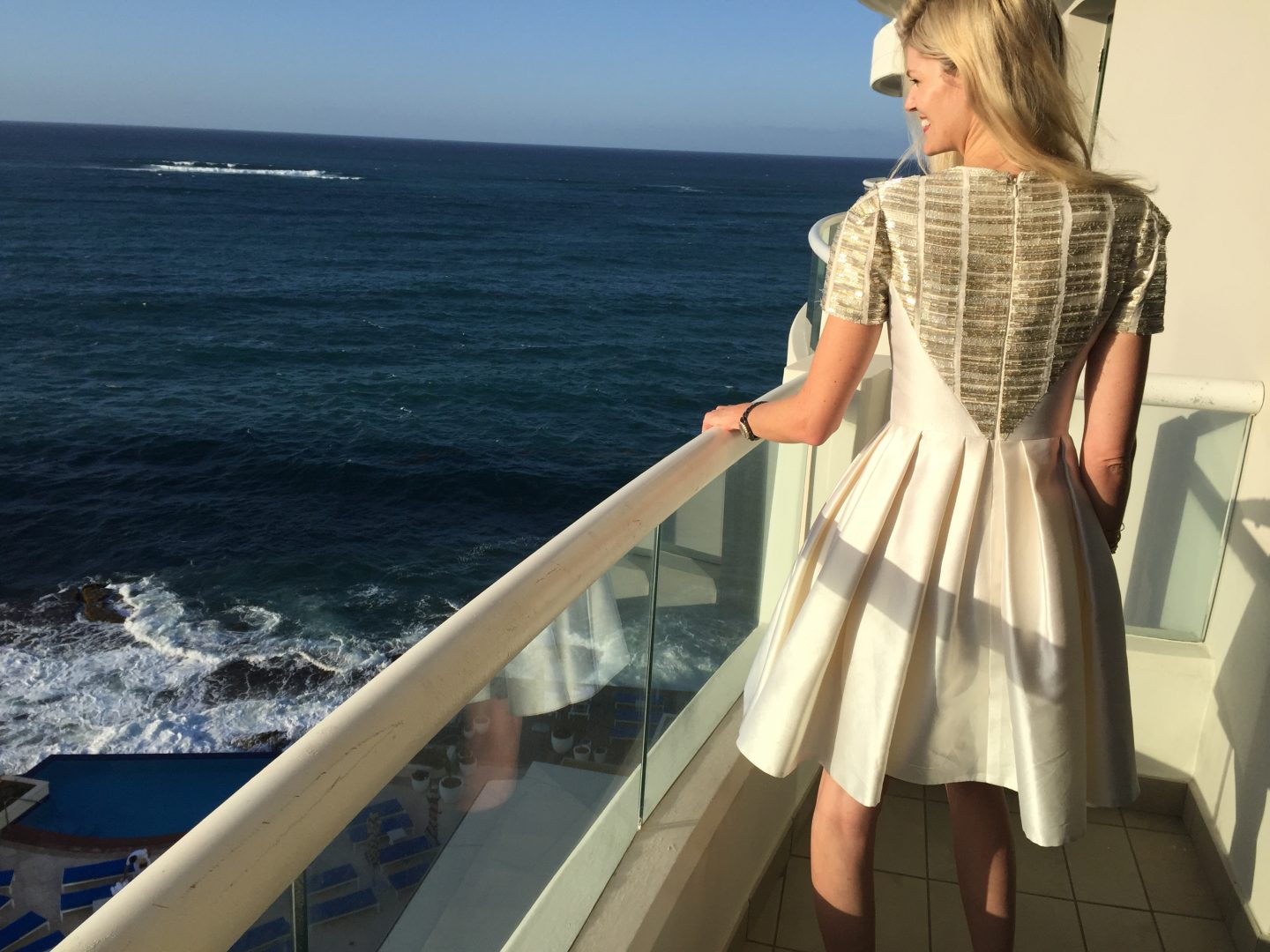 Blonde hair, gold sparkling cocktail dress on a glamorous hotel balcony overlooking the ocean