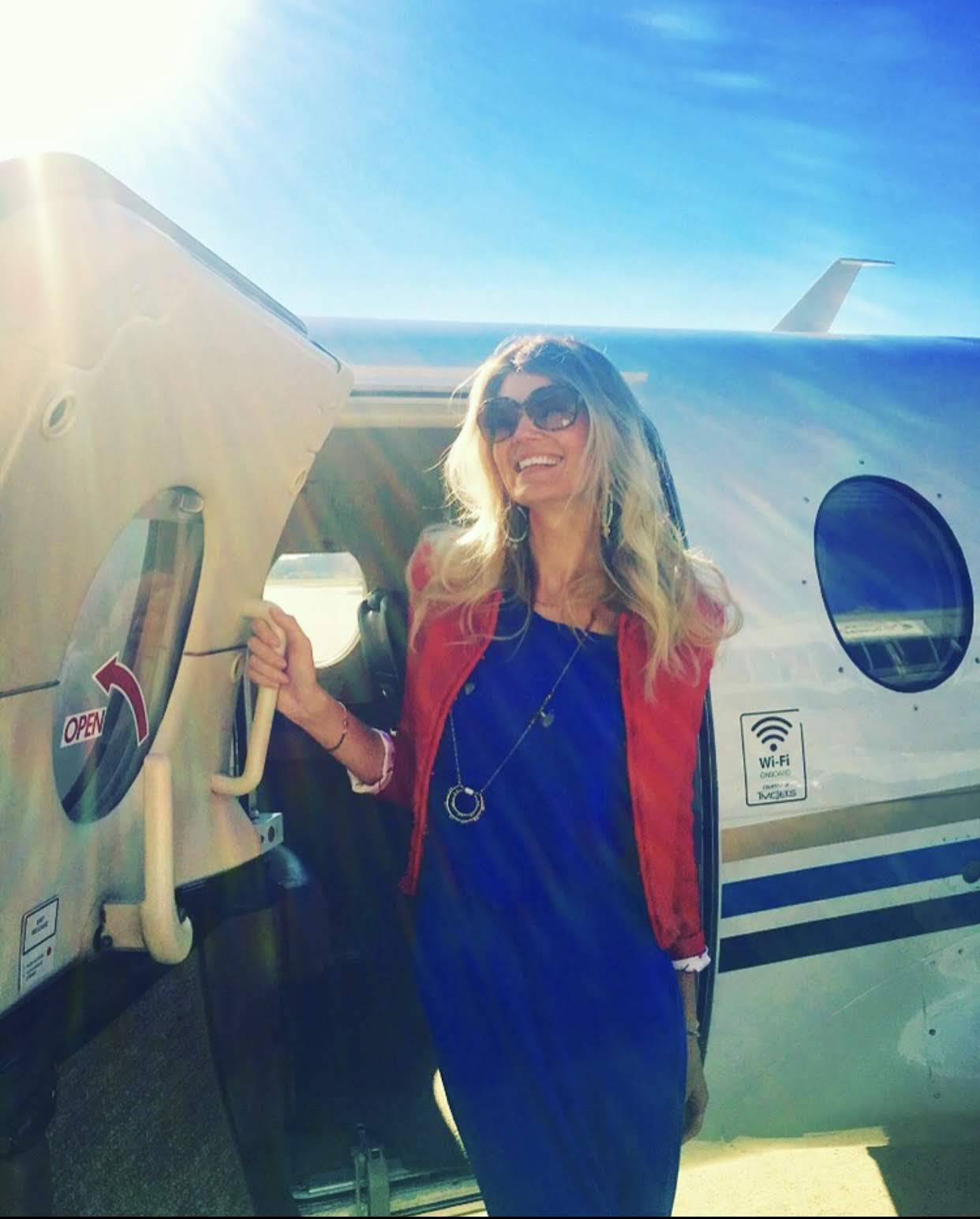 stepping out of a glamorous private plane wearing a long blue dress and sunglasses