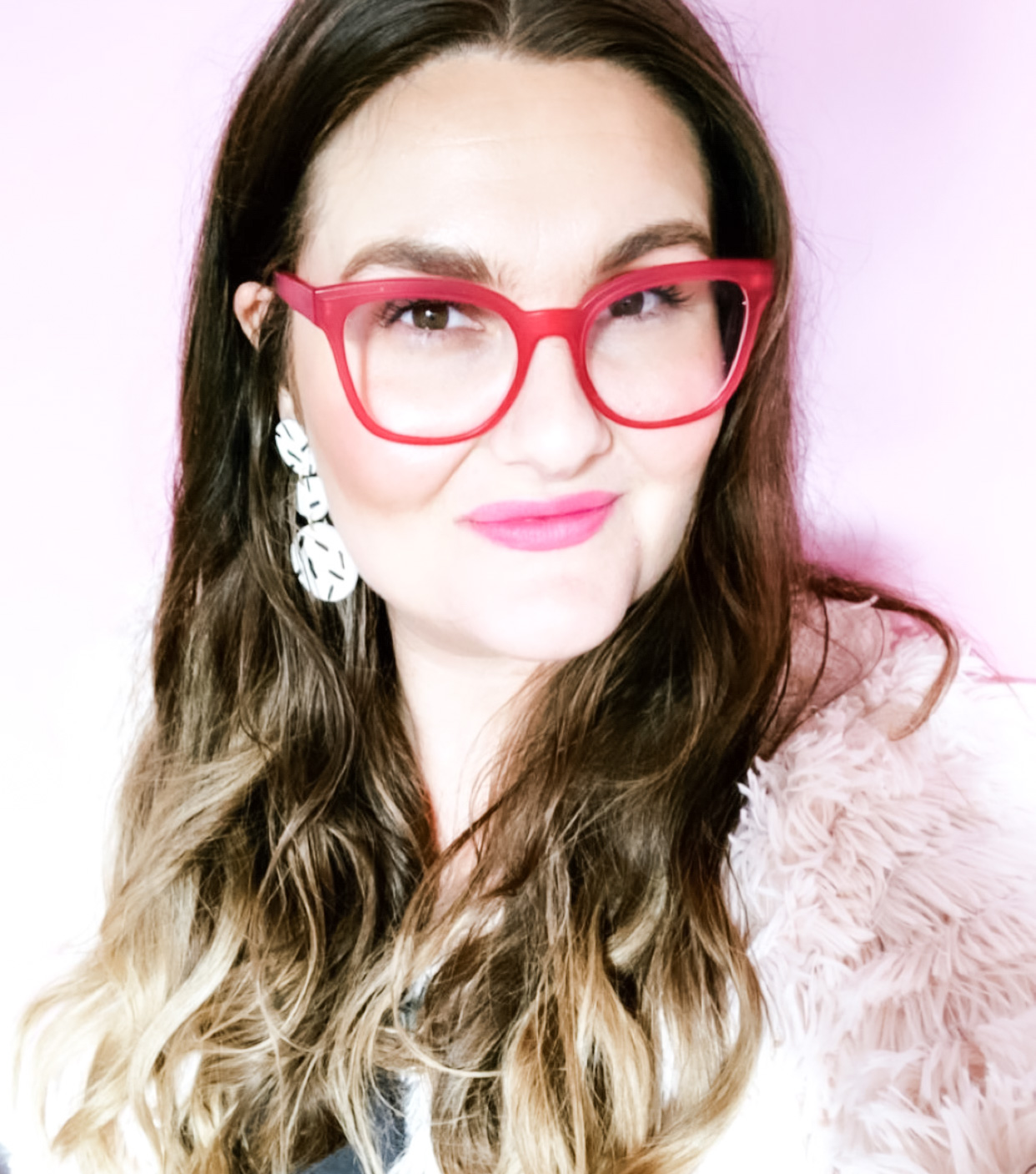 Tracy Trellis, founder of Trellis Beauty, wearing a bright pink lip color , pink glasses, in front of a pink wall in her boutique in Raleigh,NC.