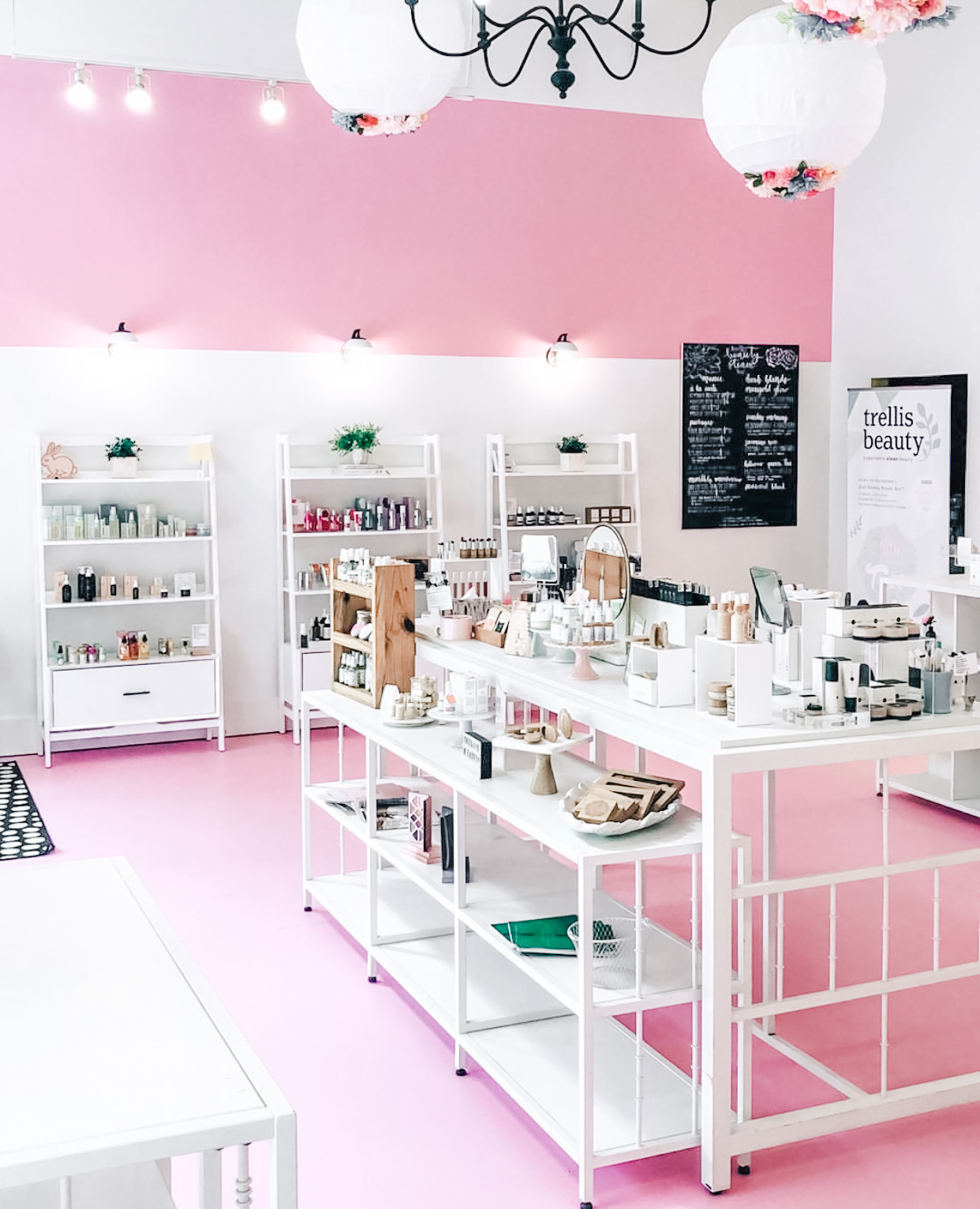 Interior of Trellis Beauty in Raleigh, NC. Pink floors, white fixtures, lots of light and pretty makeup objects on the shelves.